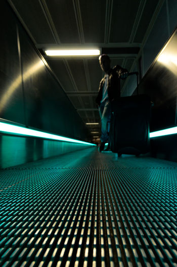 Man Standing With Luggage On Illuminated Moving Walkway