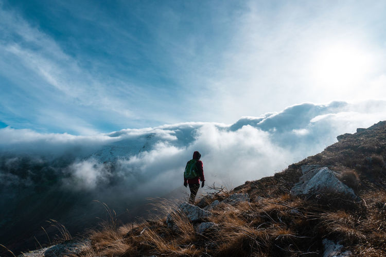 Man standing on mountain against cloudy sky