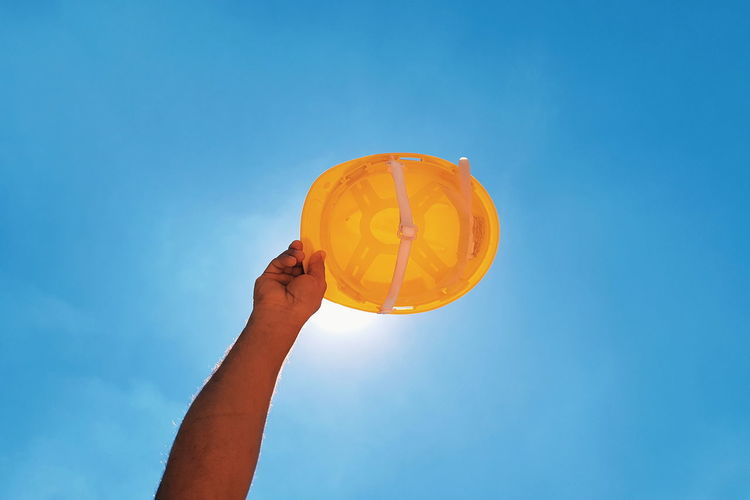 Low angle view of hand holding hardhat against clear blue sky