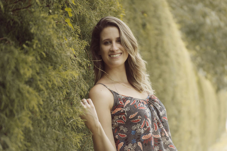 Portrait of smiling woman leaning on ivy covered wall