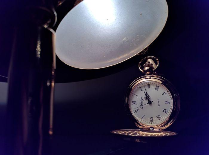 Close-up of illuminated clock on table
