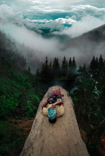Full length of man lying on tree trunk in forest