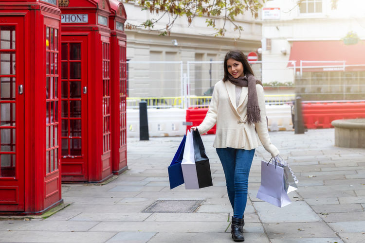 Young urban city woman with many shopping bags walks along the street in London Red Architecture One Person Lifestyles Built Structure City Bag Leisure Activity Young Adult Consumerism Beautiful Woman Hairstyle Front View Casual Clothing Real People Women Shopping Bag Telephone Booth London Shopping City Urban Attractive Concept Tourism