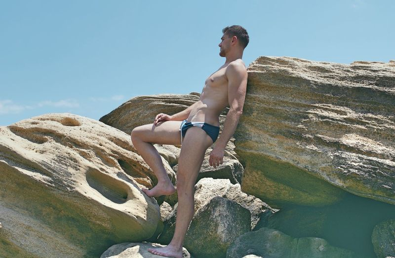 Shirtless man looking away while standing on rock against sky