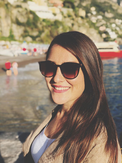 Portrait of smiling woman wearing sunglasses by lake