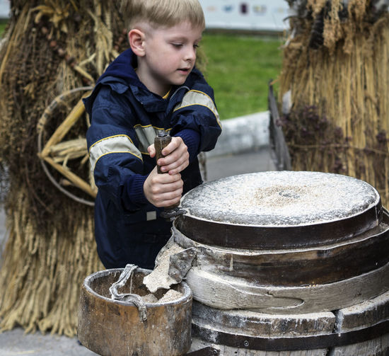 Boy grinds flour on a hand mill Boy Casual Clothing Caucasian Day Flour Focus On Foreground Full Length Grind Hand Leisure Activity Lifestyles Mill Nature Non-urban Scene Outdoors Person Sitting Tree Trunk