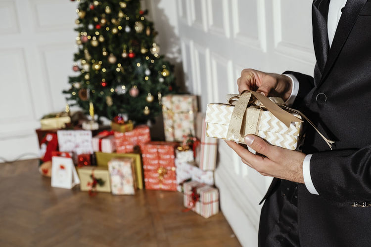 Man holding christmas present at home
