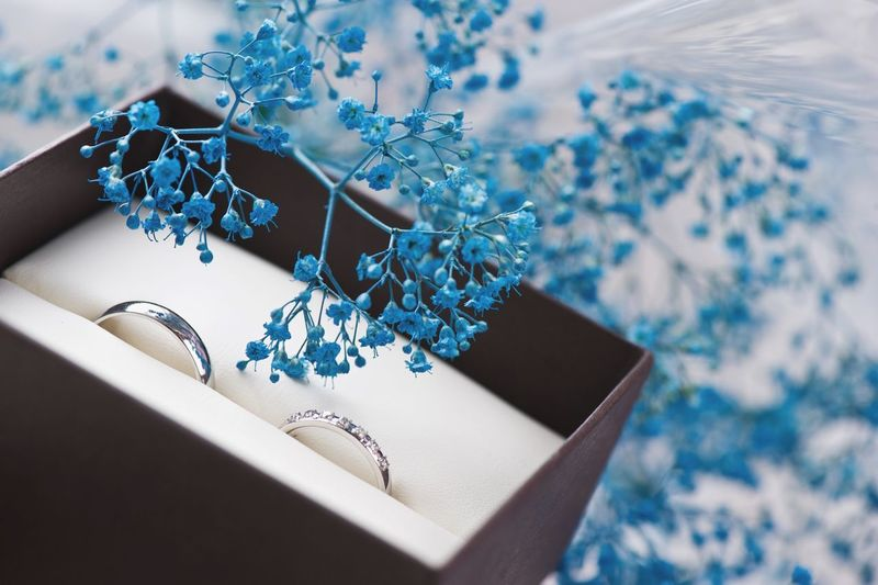 Close-up of wedding ring with artificial flower in box