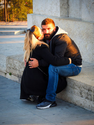 European Cities Belgrade Serbia Eastern Europe Balkans Europe Outdoors Lifestyles Men Adult Real People Togetherness Two People Young Adult Love Bonding Full Length Emotion Couple - Relationship Positive Emotion City Leisure Activity Women Young Men Hugging Sitting