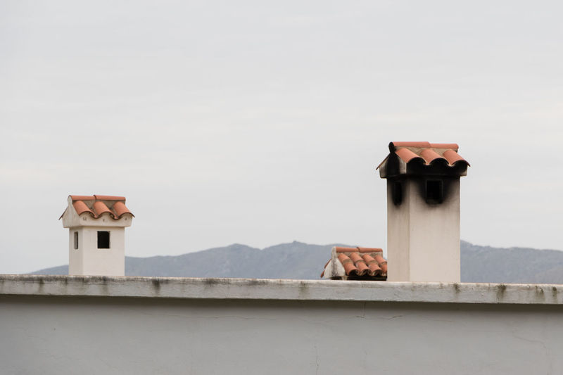 Chimneys Built Structure Architecture Building Exterior Sky No People Copy Space Day Building Outdoors Mountain Wall - Building Feature Roof Security Protection Chimney Clear Sky Tower High Section House