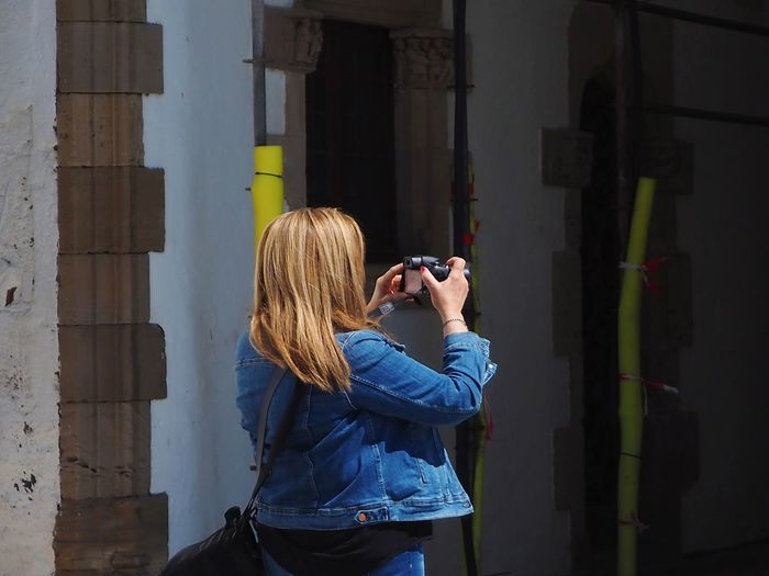 Woman photographing while standing against building