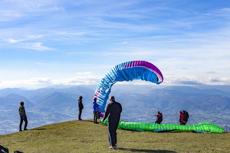 People playing against mountain range