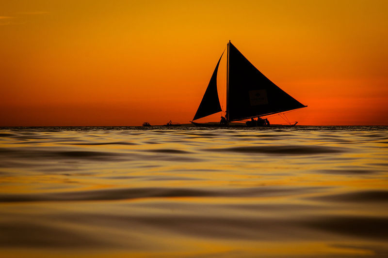 Sailboat In Sea Against Orange Sky
