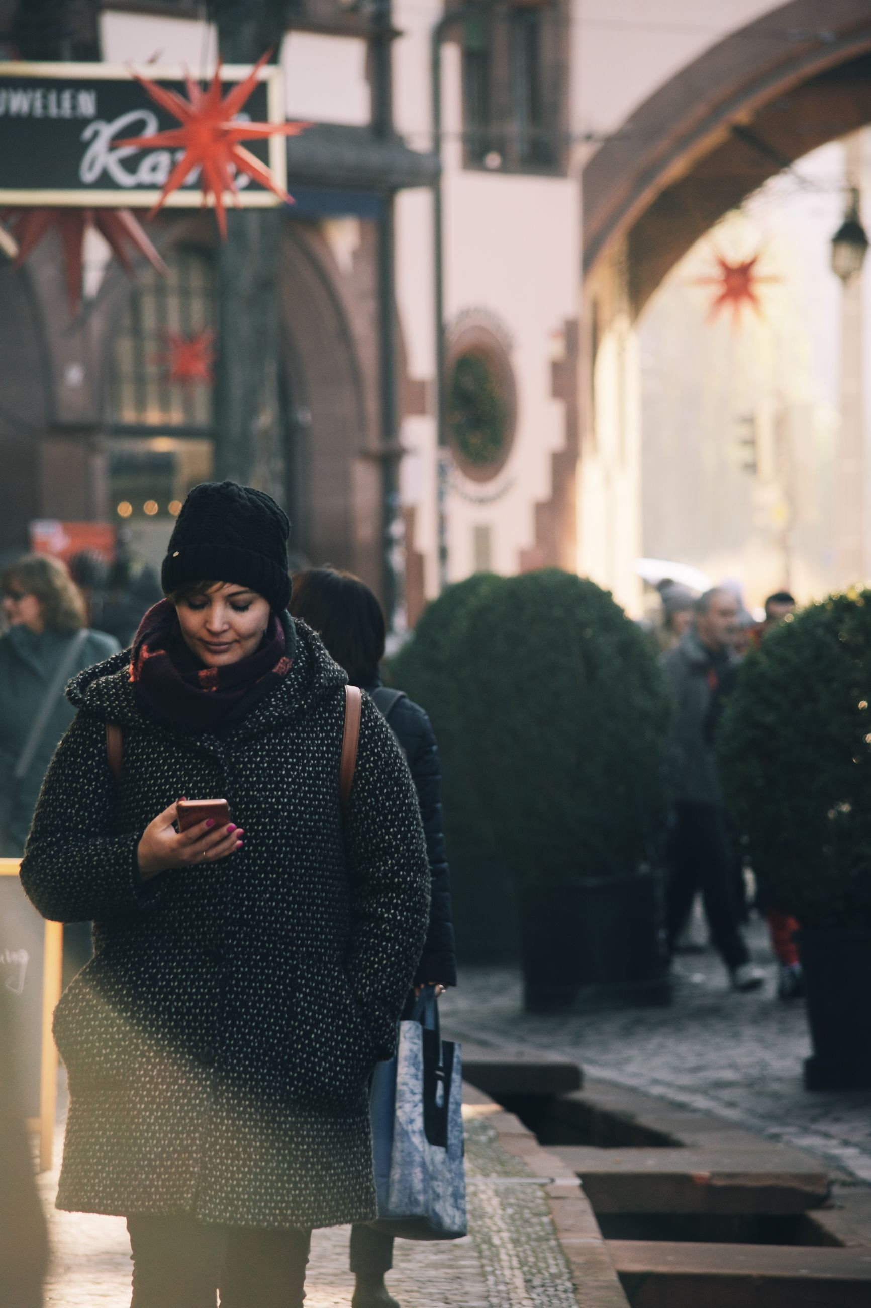 real people, architecture, one person, standing, clothing, young adult, lifestyles, communication, city, building exterior, built structure, women, warm clothing, incidental people, adult, leisure activity, day, technology, focus on foreground, wireless technology, outdoors