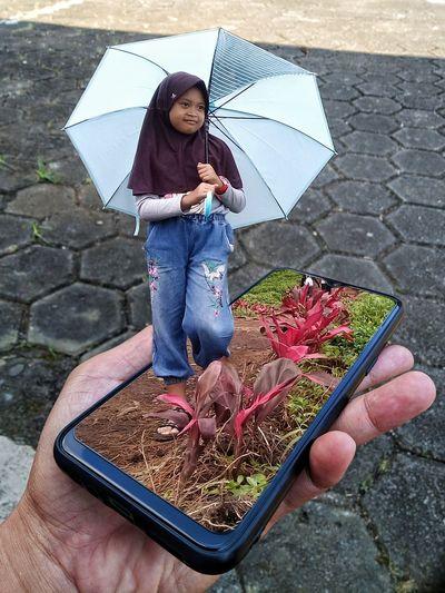 Woman holding umbrella while standing on street during rainy season