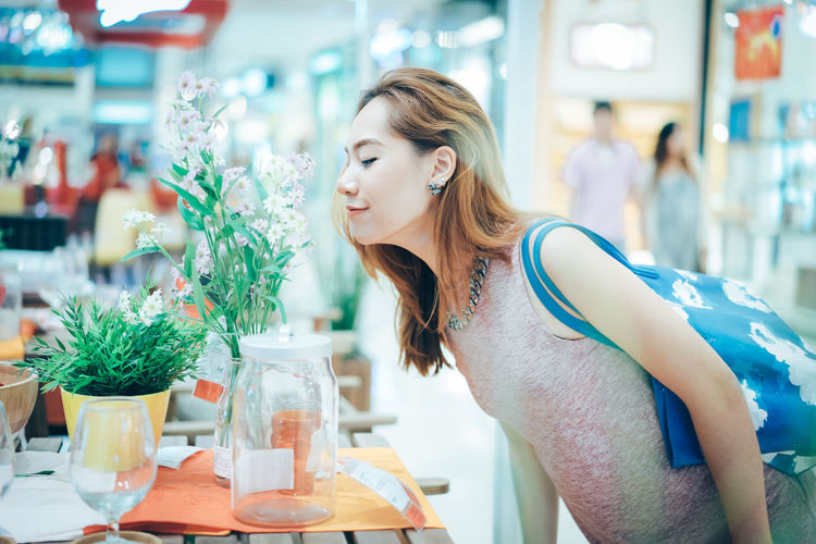 Woman smelling flowers in shopping mall