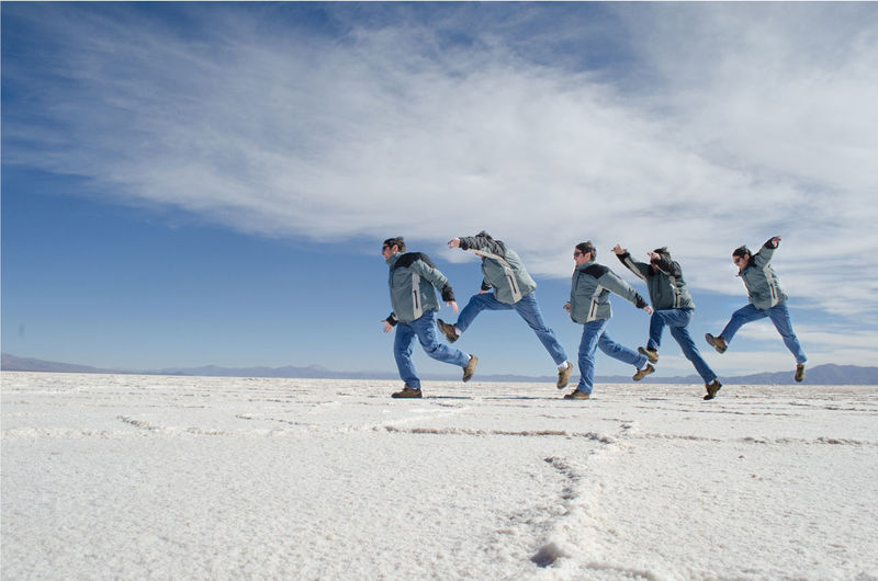 Multiple image of man jumping on salt flat against sky