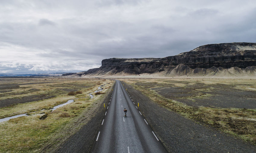 Aerial view of man skateboarding on road against sky and mountain