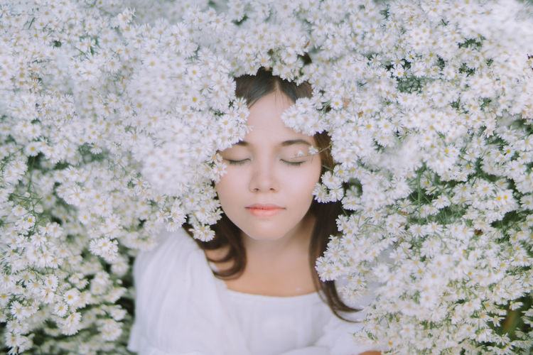 Young woman with closed eyes amidst flowering plants