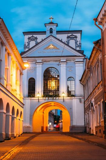 Vilnius, Lithuania. The Gate Of Dawn, The Religious, Historical And Cultural Monument, The Only Surviving Gate Of Ancient City Walls And The Chapel With Miraculous Image Of Our Lady Of Mercy. Ancient Chapel Christianity City Colour Your Horizn Exterior Famous Gate Lithuania Our Lady Of Mercy Travel Vilnius Wall Arch Architecture Blue Building Cultural Europe Evening Landmark Monument Outdoors Religion Sky