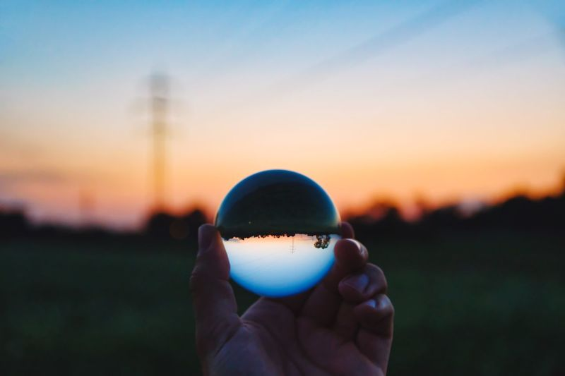 Close-up of human hand holding crystal ball against sky during sunset
