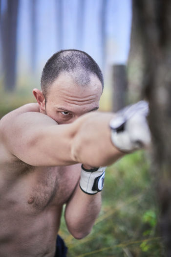 Portrait of shirtless man looking away outdoors