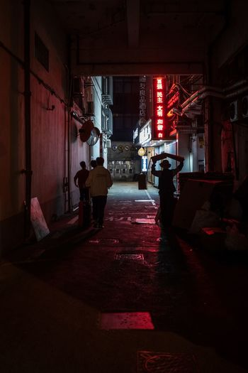 Man walking on illuminated alley amidst buildings in city at night