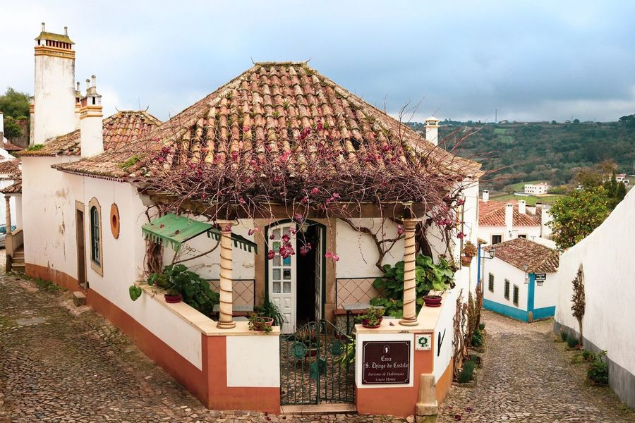 Rural Village Life Village Portugal Óbidos  Old Town Tranquility Romantic Streetphotography Street Architecture Built Structure Building Exterior Building Sky Day Residential District Plant Nature City House Tree Outdoors Cloud - Sky No People Direction Roof Town The Way Forward Roof Tile