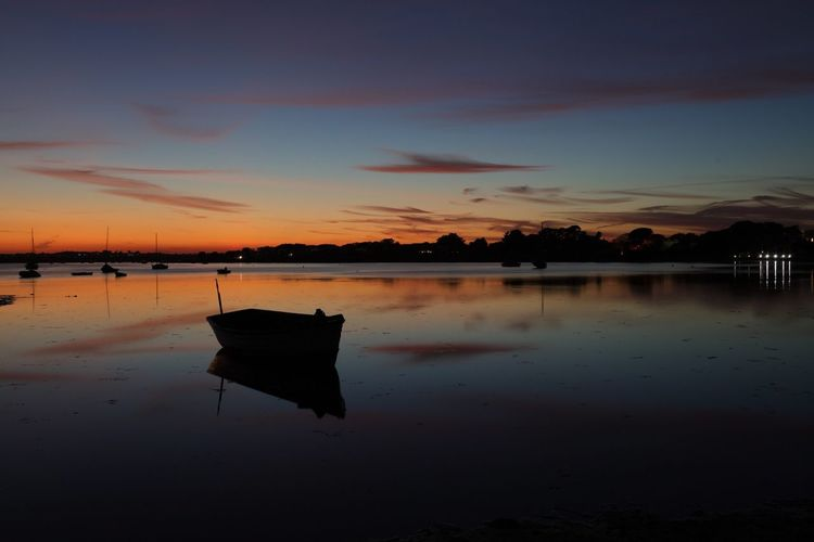 Moored Boat In Calm Lake Against The Sky