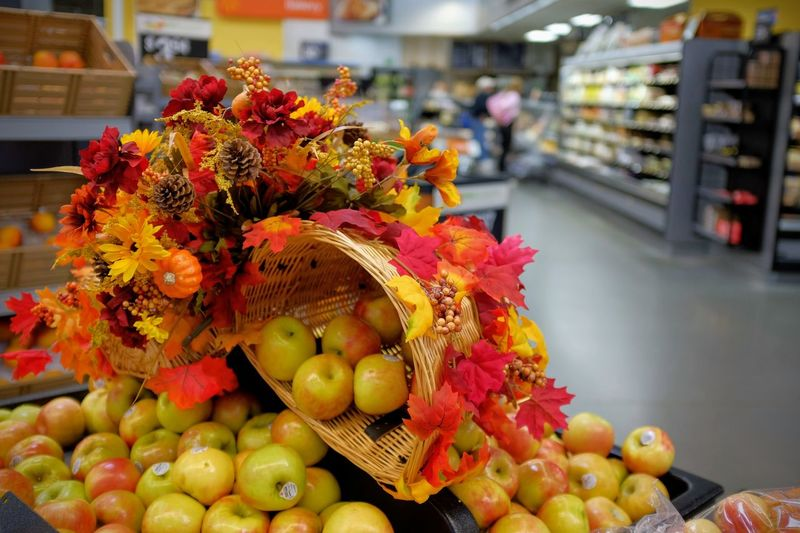 Close-Up Of Apples With Maple Leaves In Supermarket During Autumn