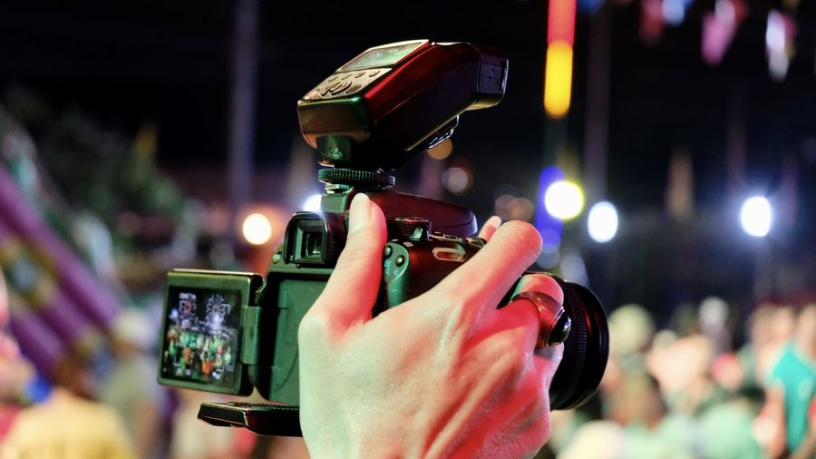 Cropped hand of person photographing at night