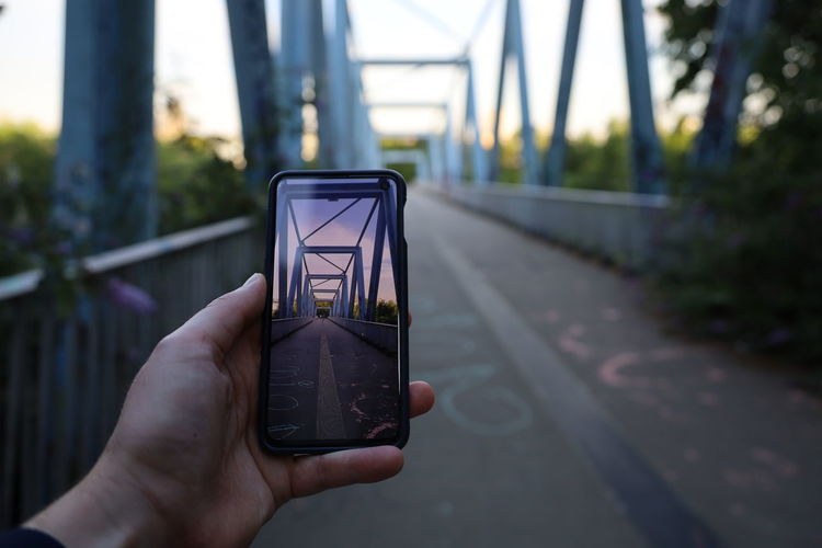Hand of person using mobile phone to take picture of a bridge