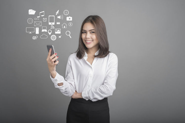 Digital composite image of businesswoman and computer icons against gray background
