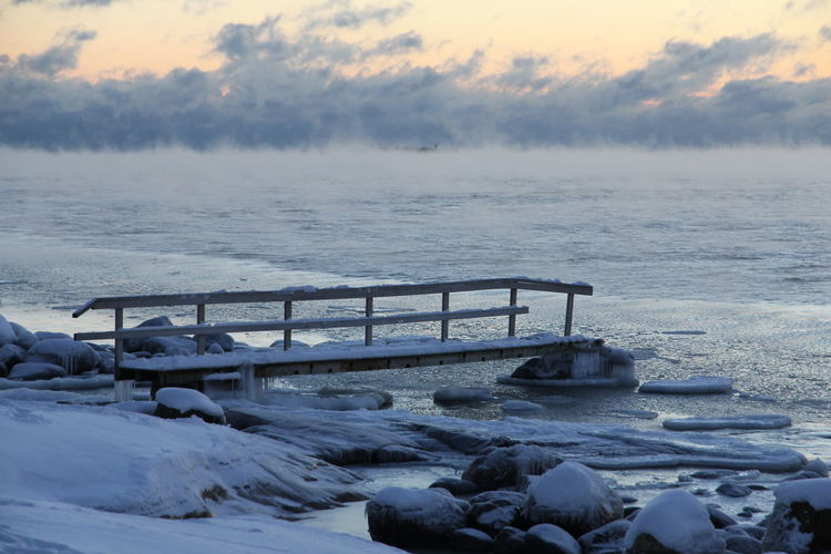 Scenic View Of Frozen Lake Against Dramatic Sky