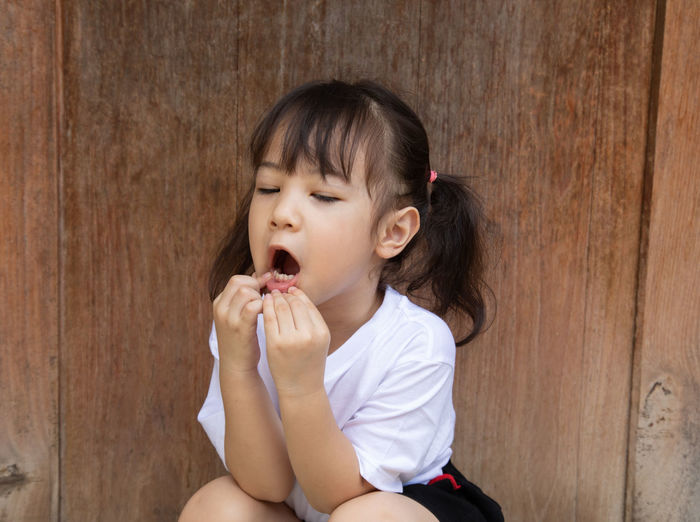 Cute girl with mouth open sitting against wall