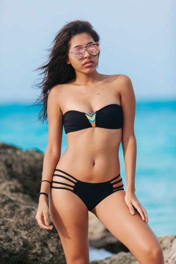 Woman in bikini and sunglasses standing at beach