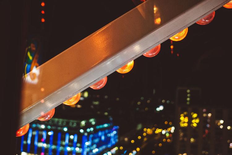 Close-up of illuminated lighting equipment in city at night