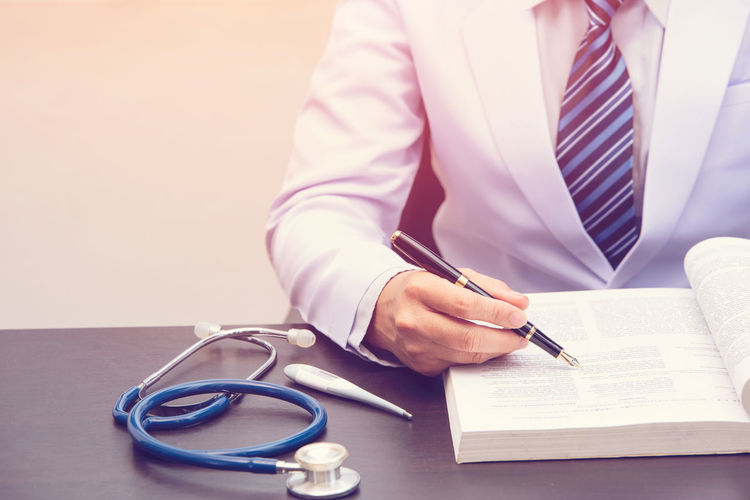 Midsection of doctor writing prescription on book at table