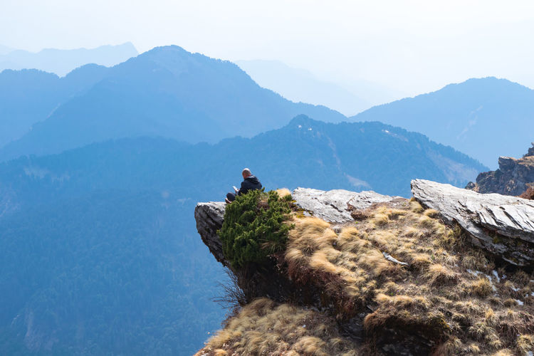 man sitting on the edge of a hill and relaxing Edge Of The World The Traveler - 2018 EyeEm Awards Hiking Trekking Activity Adventure Beauty In Nature Chandrashila Trek Hill Incredible India Leisure Activity Men Mountain Mountain Peak Mountain Range Nature Non-urban Scene One Person Outdoors Real People Scenics - Nature Sky Tranquil Scene Tranquility Uttarakhand A New Beginning