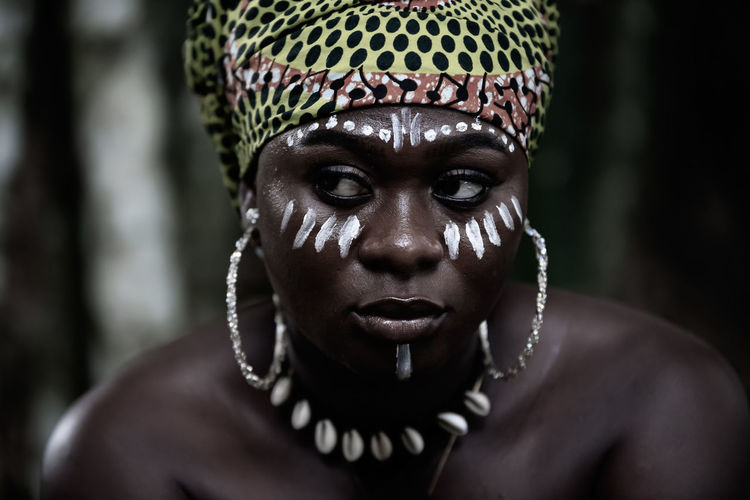 African woman sitting in the aburi forest in ghana with white painting on her face and headdress