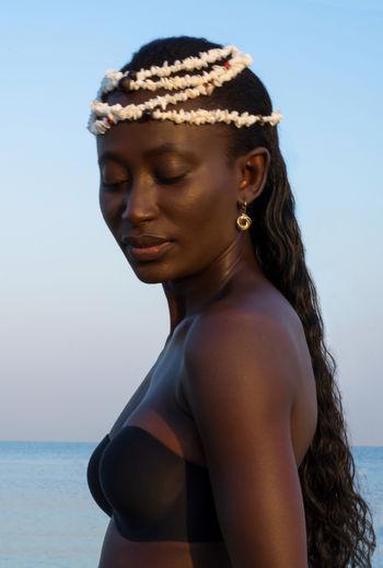 Portrait of beautiful woman on beach against sky