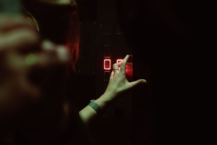 Cropped Hand Of Woman Pressing Push Button In Elevator