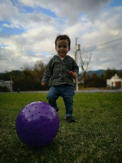 Portrait of cute baby boy playing with ball standing on grassy field