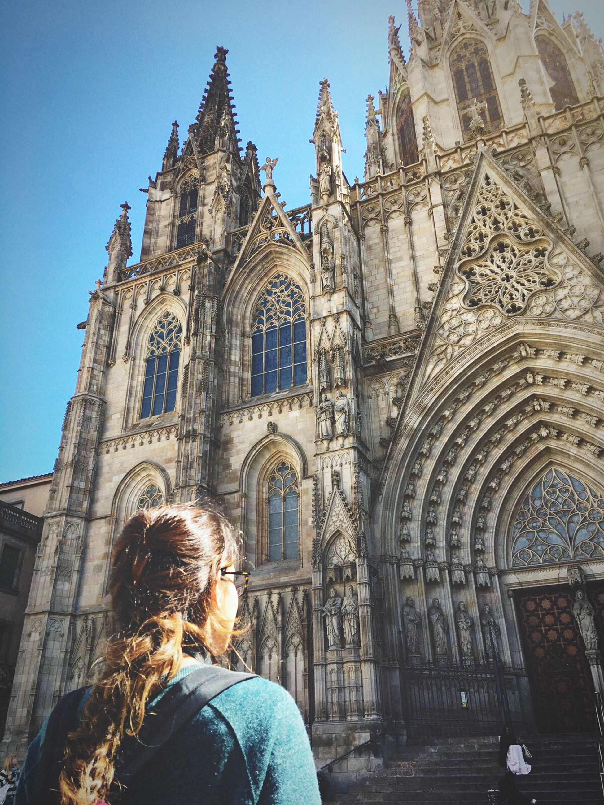 religion, place of worship, spirituality, architecture, real people, building exterior, built structure, leisure activity, one person, day, women, sunlight, history, outdoors, lifestyles, rear view, low angle view, men, standing, sky, people