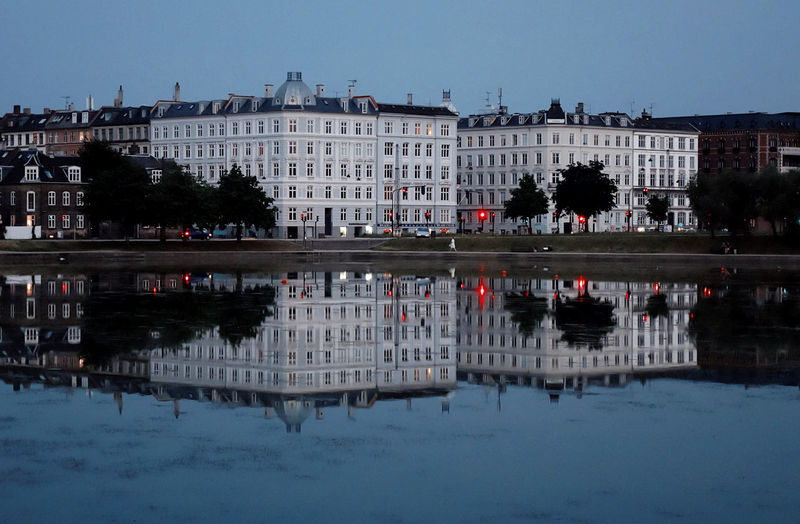 Buildings Reflecting In River At Dusk