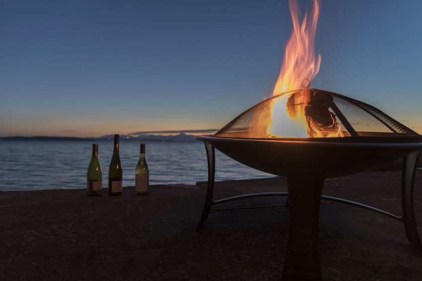 Wine bottles and flames in a fire pit by the sea at sunset on the Fourth of July Alcohol Backyard Beauty In Nature Bottles Coast Drinking Entertaining Fire Fireplace Flames Flicker Fourth Of July Golden Hour Home House Outdoor Party Pit Sea Shore Summer Sunset Vibrant Color Wine