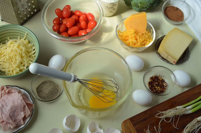 Overhead--egg yolks, whisk in glass mixing bowl--whole unbroken eggs, cheddar cheese, Gruyere cheese, shredded Swiss cheese, black pepper, red pepper, nutmeg in small glass dishes, broccoli, Grape tomatoes in bowl in back, green onions on cutting board--ingredients for making Quiche Assortment Bowl Choice Cooking Cooking At Home Food Freshness Healthy Eating High Angle View Homemade Indoors  Ingredients No People Preparation  Preparing Food Quiche Selective Focus Table Tomatoes Variation