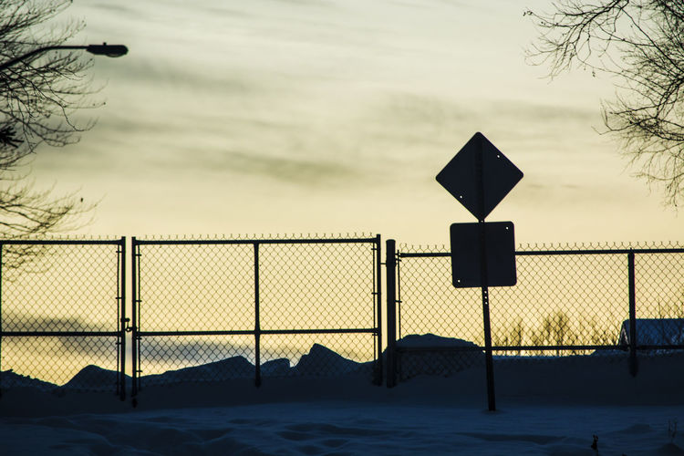 Road sign against sky during winter