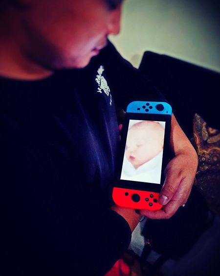 Gamer's child Wireless Technology Connection One Man Only Human Body Part Adult Holding Technology Portable Information Device Communication Mobile Phone Smart Phone Telephone Portability Men People One Person Close-up Day Nintendoswitch Handheld Gaming Console Gamer Nintendo 12switch Player