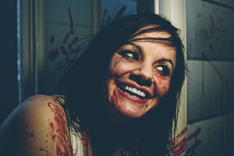 Close-up of smiling criminal with blood on face